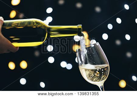 Wine pouring in glass on bokeh background