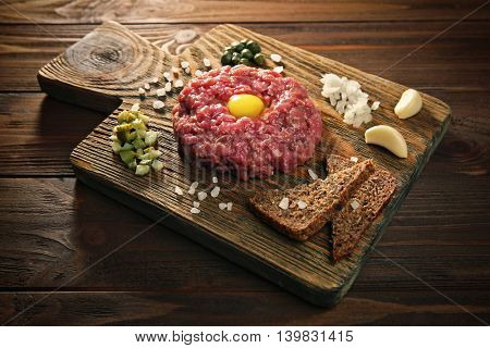 Steak tartar with chopped onion and pickles on wooden board