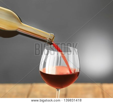 Red wine pouring in glass on grey background