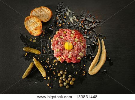 Steak tartar with bread and pickles on black background