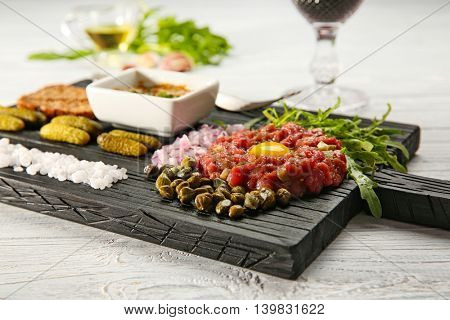 Steak tartar with chopped onion and herbs on wooden board
