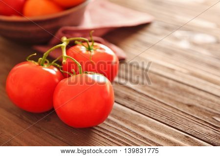 Bunch of red tomatoes on wooden table, close up