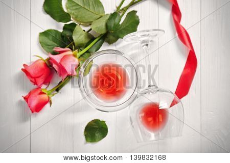 Glasses  with wine and flowers on a wooden background