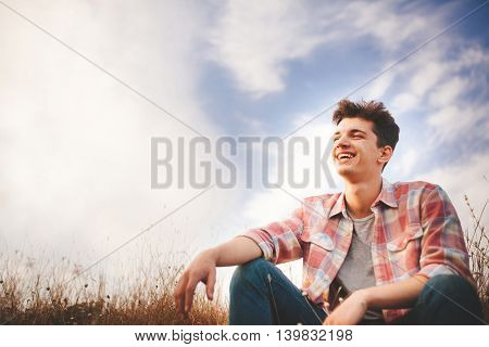 Handsome teenager boy wearing casual shirt. Happy smiling young man sitting on grass on sky background