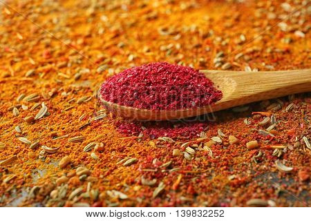 Sumac in wooden spoon on mixed spices background