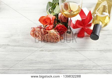 Bottle of wine, gift boxes and roses on a wooden background