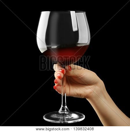 Female hand holding glass of wine on black background