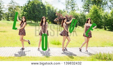 four young pretty smiling girls holding letters with the word love outdoor on sunny summer day