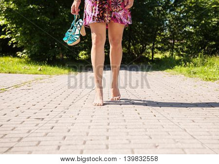 young woman goes barefoot on the sidewalk and holding a shoe on summer day