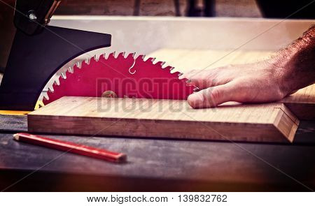 detail of table saw blade and human hand in dangerous position