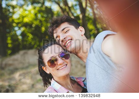 Young couple making a selfie outdoors. Teenage girl wearing sunglasses and young man having fung with camera on a suny day. Young people making a selfie