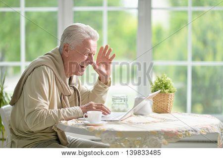 Portrait of a happy senior man using laptop