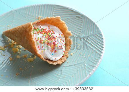 Dessert in ice cream cone on light blue plate