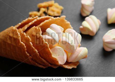 Dessert in ice cream cone on dark background