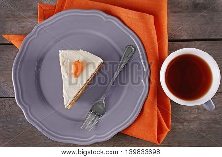 Piece of carrot cake with a cup of tea on wooden table