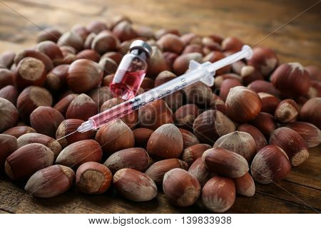Syringe and hazel nuts on wooden table