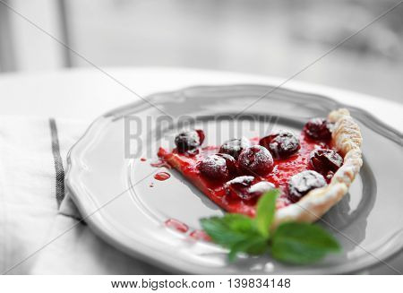 Cherry pie slice on gray plate, close up