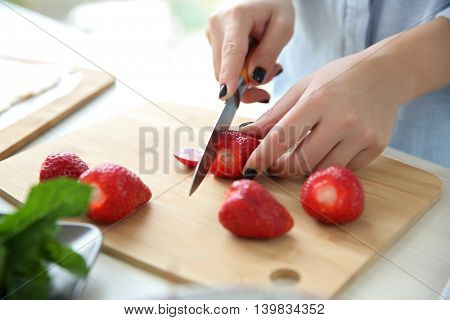 Woman slicing strawberries for dessert in kitchen