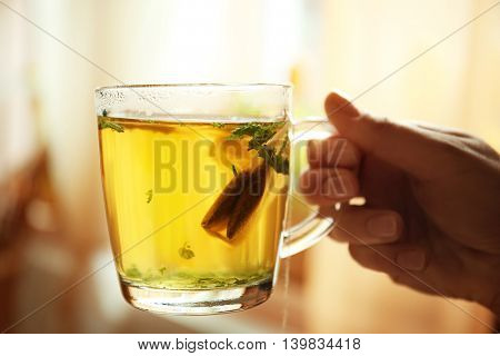 Female hand holding cup with green tea on blurred kitchen background