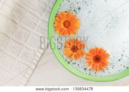 Soothing cleansing foam bath with calendula. Bright flowers, aromatic foam in green bowl, white towel background. Top view.