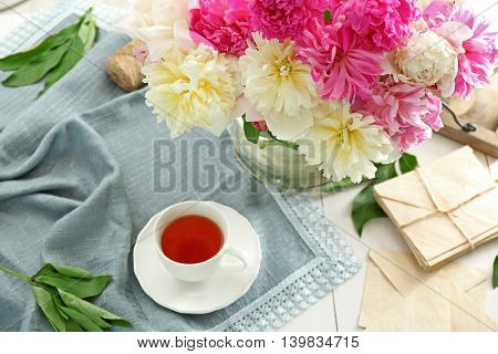Composition with peony flowers and cup of tea on table closeup