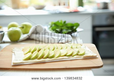 Apple slices on puff dough in kitchen