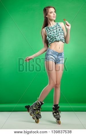 Very attractive woman with lollipop in sexy outfit posing on green studio background wearing inline rollerskates