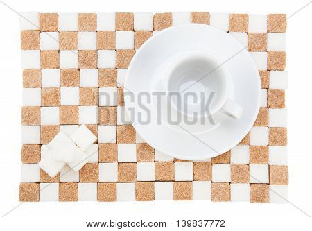 empty coffee cup on a saucer with four white sugar cubes on a stand of white and brown sugar. Isolated on white.