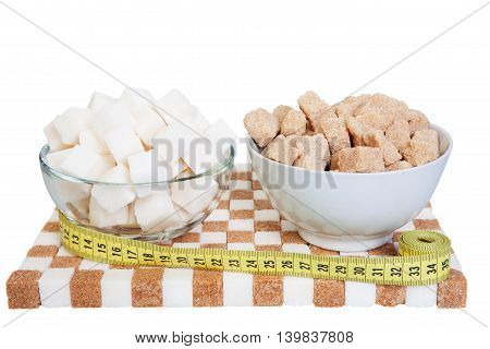 two bowls with white and brown sugar on a stand of sugar and a measuring tape. The concept of excess sugar. Isolated on white background.