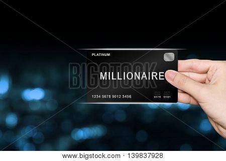 hand picking millionaire platinum card on blur background