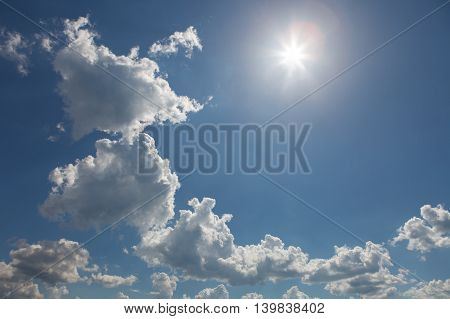 Chain of cumulus clouds with sun. Blue sky.
