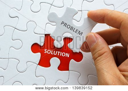 Hand holding piece of jigsaw puzzle with word PROBLEM SOLUTION.