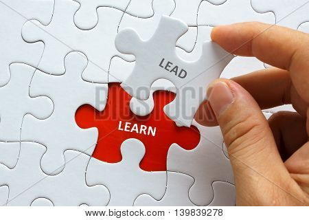 Hand Holding Piece Of Jigsaw Puzzle With Word Lead Learn.