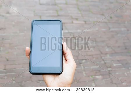 Modern black mobile phone in a woman's hand. Urban background