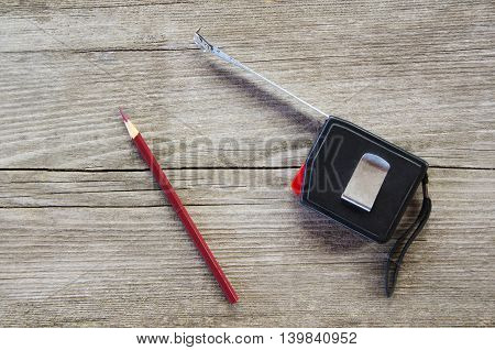 Measuring roulette tape for measurements with a pencil on a wooden background