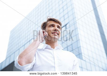 Happy young businessman stading near skyscraper and talking on cell phone