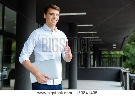 Smiling successful young businessman holding laptop and showing thumbs up