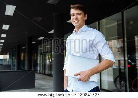 Cheerful attractive young businessman standing ang holding laptop