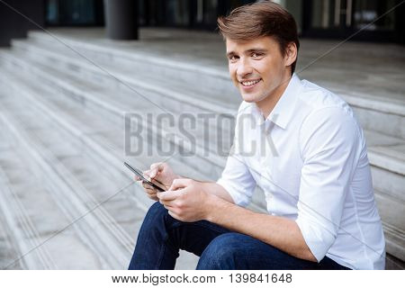 Happy young man sitting on stairs and using tablet outdoors