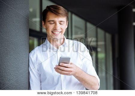 Smiling young businessman standing and using cell phone near business center