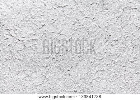 Decorative paper imitates the old gray plaster or vintage silver surface of the facade. White painted rough wall.