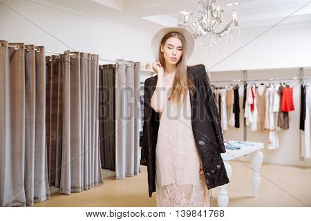 Stylish young woman in dress, jacket and hat standing in showroom