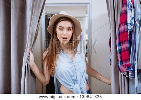 Portrait of happy pretty young woman trying on clothes in dressing room of clothing shop