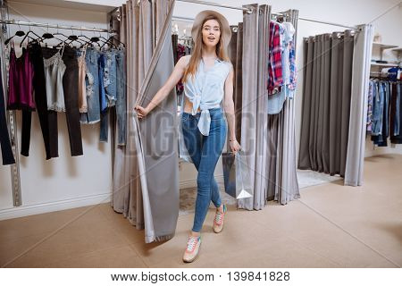 Smiling attractive young woman with shopping bag going out of fitting room