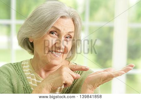 happy Senior woman portrait at home pointing by her hands