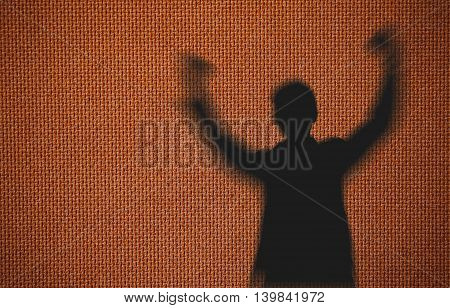 Silhouette of man showing his hand on soft brown background, Successful business concept.
