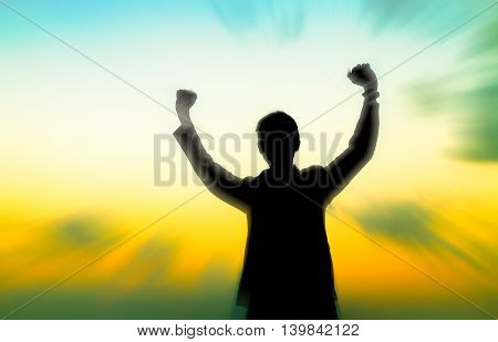 Motion silhouette of man showing his hand on sunset sky background, Successful business concept.