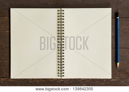 Brown open book with pencil on wood table