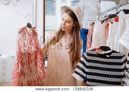 Pensive young woman thinking and choosing clothes in shop