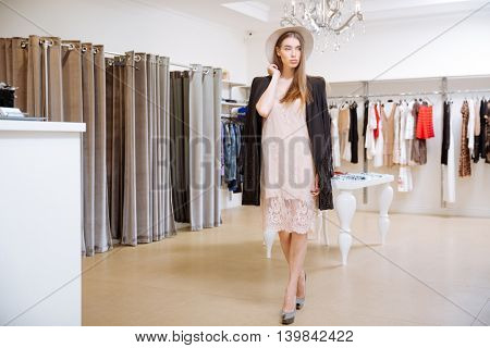 Fashionable beautiful young woman standing in clothig shop